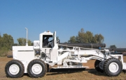 A Medium Construction Road Grader modified with a Mine Protected Cab