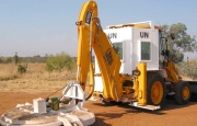 A Backhoe loader modified as vegetation cutter with blast protection shielding